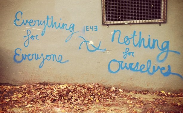 "image of text spray painted in an alley, it says ""everything for everyone, nothing for ourselves"""